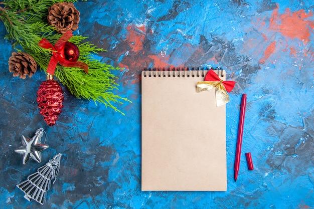 Vista superior de galhos de pinheiros com pinhas penduradas no caderno de enfeites e caneta vermelha na superfície azul-vermelha