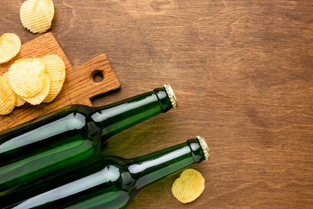 Vista superior de garrafas de cerveja com batatas fritas