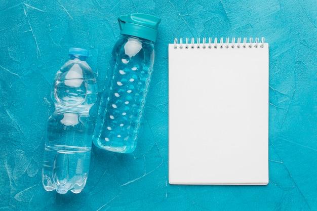 Vista superior de garrafas de fitness e bloco de notas