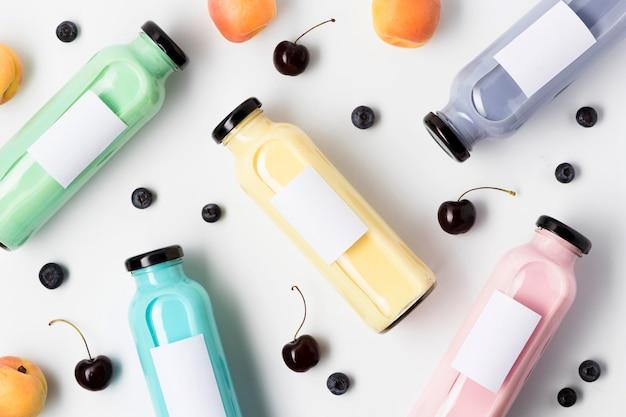 Vista superior de garrafas de suco de frutas multicoloridas com cerejas e mirtilos