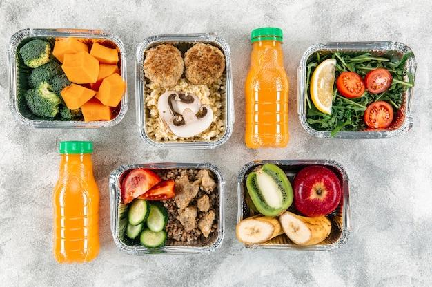 Vista superior de garrafas de suco de laranja com refeições em caçarolas