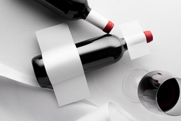 Vista superior de garrafas de vinho translúcidas e copos com rótulos em branco