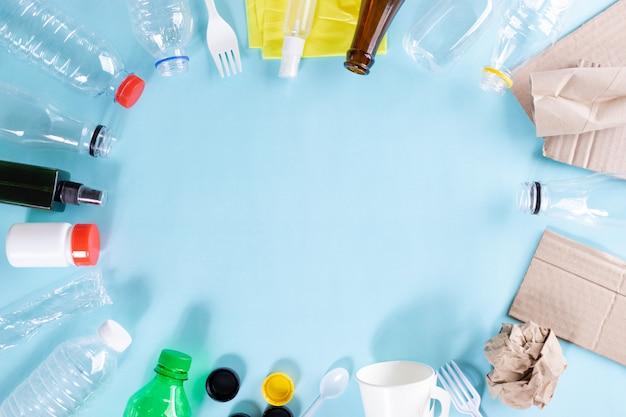 Vista superior de garrafas, reciclagem de resíduos, triturador de lixo sobre fundo azul. dia mundial do meio ambiente