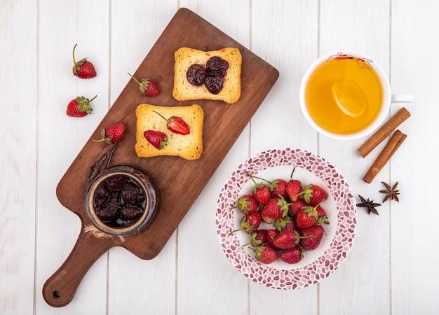 Vista superior de geléia de morango em uma placa de cozinha de madeira com pão torrado com morangos frescos e paus de canela em um fundo branco de madeira