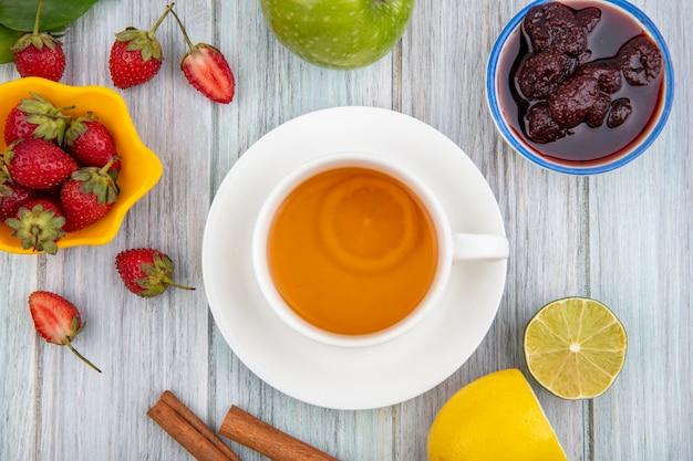 Vista superior de geleia de morango em uma tigela com uma xícara de chá com morangos frescos em uma tigela amarela sobre um fundo cinza de madeira