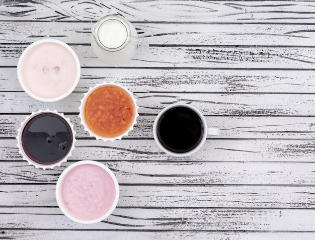 Vista superior de geléia e iogurte com leite, café e cópia espaço na superfície de madeira branca horizontal