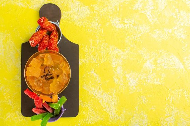 Vista superior de geléias amarelas com torrão e marmeladas na superfície amarela