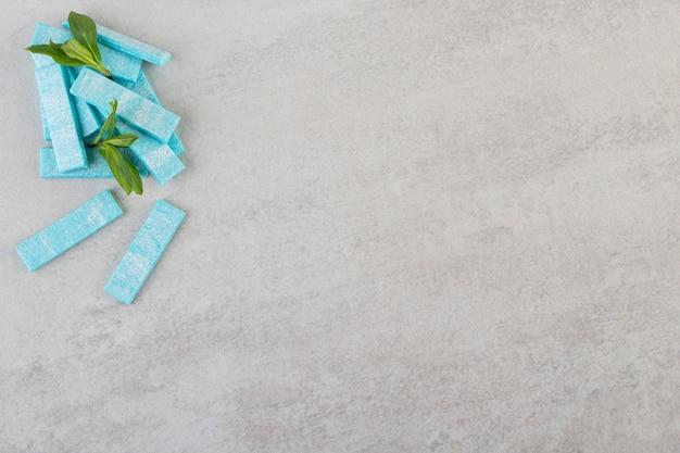 Vista superior de gomas agridoces com folhas de hortelã na superfície cinza