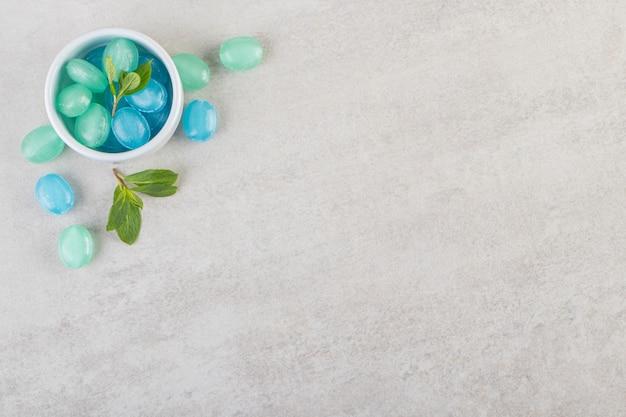 Vista superior de gomas azuis com folhas de hortelã em fundo cinza.