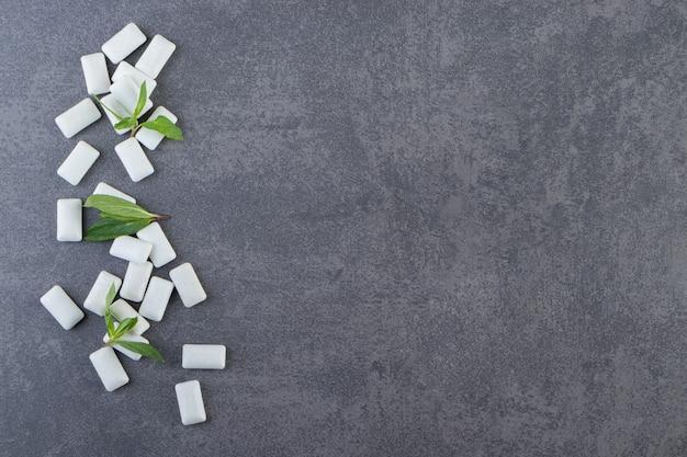Vista superior de gomas brancas com folhas de hortelã em fundo cinza.