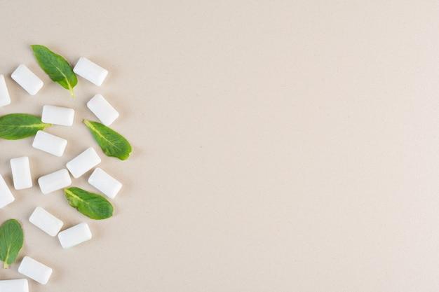 Vista superior de gomas brancas com folhas de hortelã no creme.