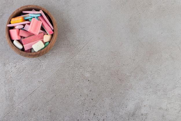Vista superior de gomas coloridas em uma tigela de madeira.