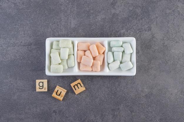 Vista superior de gomas coloridas no prato e letras de goma no chão.