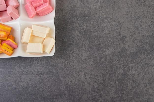 Vista superior de gomas coloridas no prato sobre fundo cinza.
