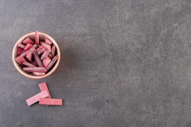 Vista superior de gomas rosa em uma tigela de madeira sobre uma superfície cinza