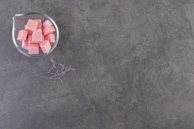 Vista superior de gomas rosa em uma tigela de vidro sobre uma superfície cinza