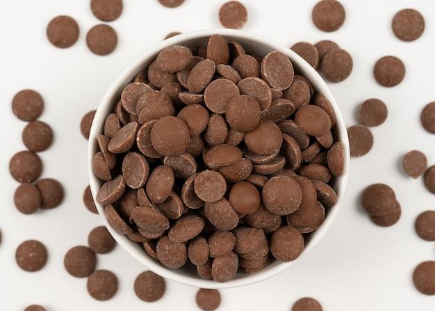 Vista superior de gotas de chocolate ao leite em uma tigela isolada no branco em alta resolução