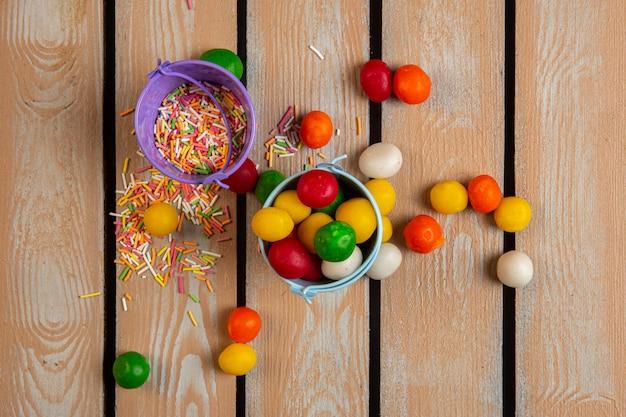 Vista superior de granulado colorido e doces em pequenos baldes