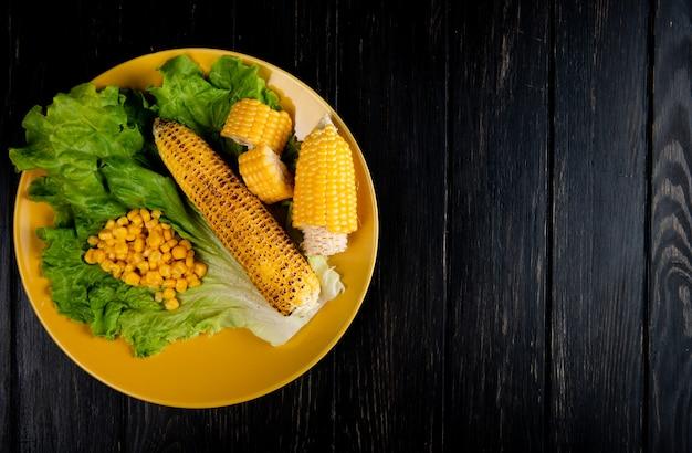 Vista superior de grãos cortados e inteiros e sementes de milho com alface em placa no lado esquerdo e preto com espaço de cópia