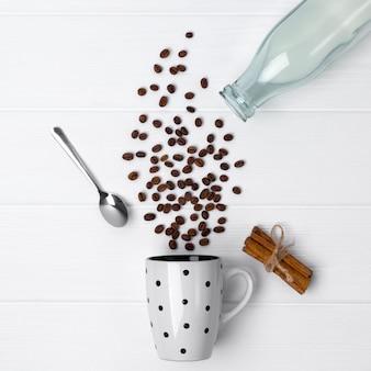 Vista superior de grãos de café, derramando fora do copo de bolinhas com colher e garrafa de leite