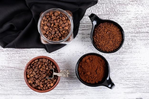 Vista superior de grãos de café e café instantâneo em copos na mesa branca