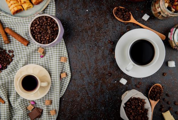 Vista superior de grãos de café e xícaras de café sobre fundo preto, com espaço de cópia