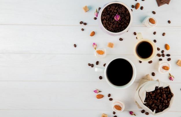 Vista superior de grãos de café em um saco e xícaras de café sobre fundo branco, com espaço de cópia