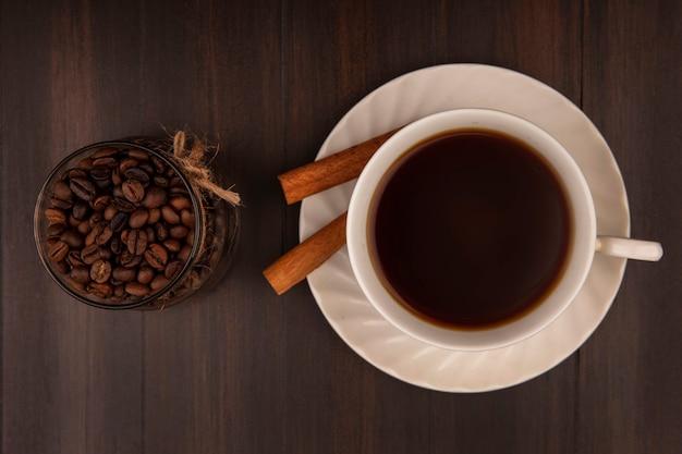 Vista superior de grãos de café em uma jarra de vidro com uma xícara de café com paus de canela em uma parede de madeira