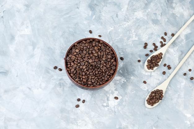 Vista superior de grãos de café em uma tigela e colheres de madeira em um fundo de gesso cinza