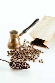 Vista superior de grãos de café espalhados ao redor, um saco de papelão, uma esponja e uma cafeteira rústica