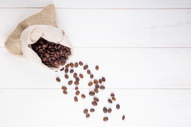 Vista superior de grãos de café espalhados de um saco em fundo branco de madeira, com espaço de cópia