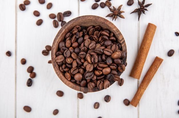 Vista superior de grãos de café frescos em uma tigela de madeira com paus de canela e anis em um fundo branco de madeira