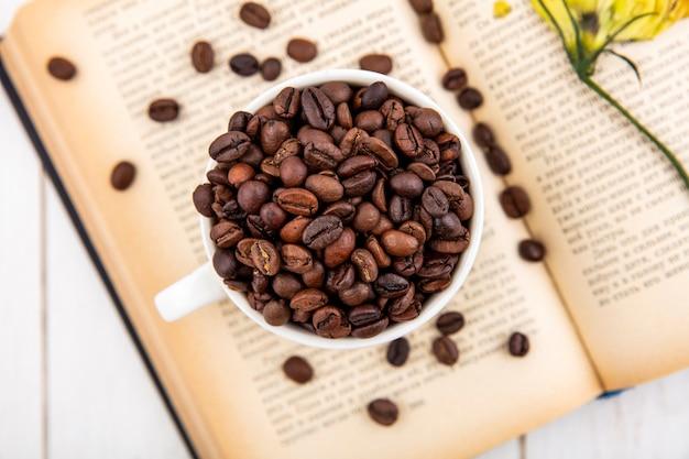 Vista superior de grãos de café frescos em uma xícara branca em um fundo branco de madeira