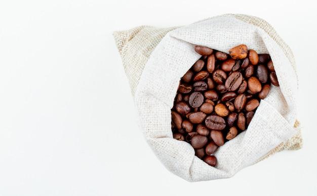 Vista superior de grãos de café marrons em um saco em fundo branco, com espaço de cópia