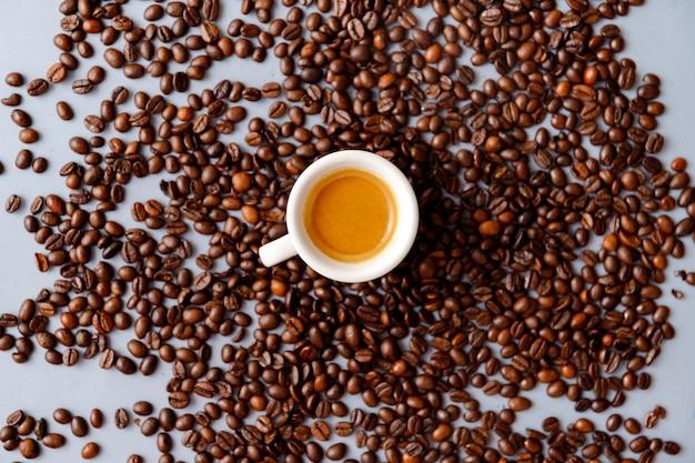 Vista superior de grãos de café torrados em uma caneca