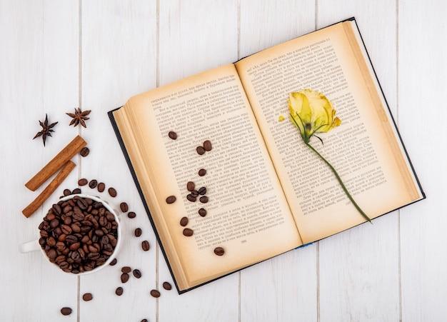 Vista superior de grãos de café torrados em uma xícara branca com paus de canela e anis em um fundo branco de madeira