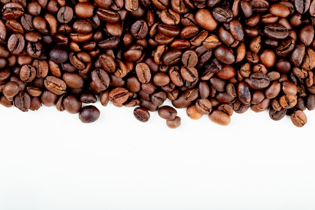 Vista superior de grãos de café torrados, espalhados sobre fundo branco, com espaço de cópia