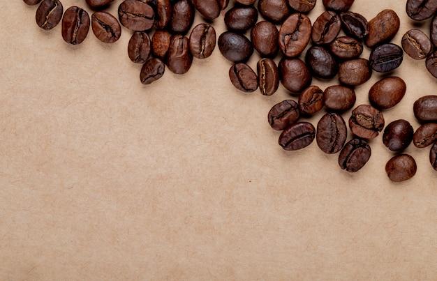 Vista superior de grãos de café torrados, espalhados sobre fundo de textura de papel pardo com espaço de cópia