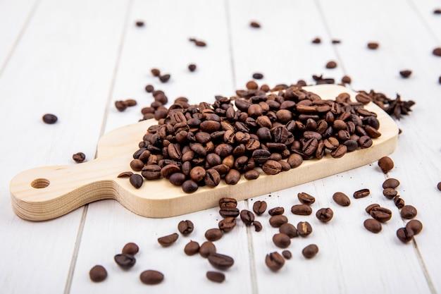 Vista superior de grãos de café torrados frescos em uma placa de cozinha de madeira em um fundo branco de madeira