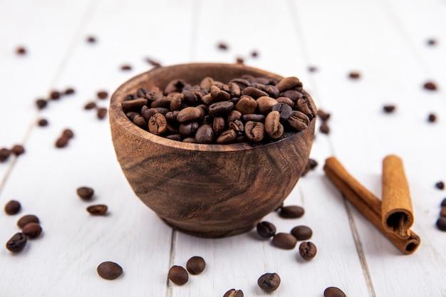 Vista superior de grãos de café torrados frescos em uma tigela de madeira com paus de canela em um fundo branco