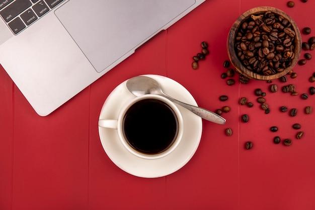 Vista superior de grãos de café torrados frescos em uma tigela de madeira com uma xícara de chá em um fundo vermelho