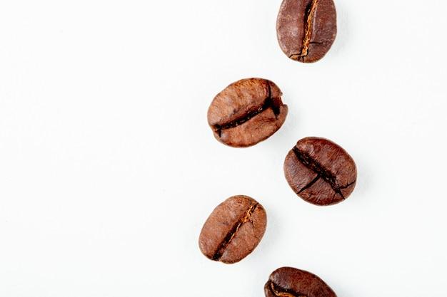 Vista superior de grãos de café torrados, isolado no fundo branco, com espaço de cópia