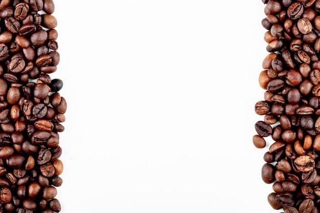 Vista superior de grãos de café torrados no fundo branco, com espaço de cópia