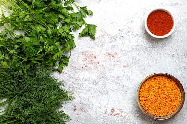 Vista superior de grãos de laranja crus chamados merci com verduras no fundo branco sopa de feijão comida de farinha crua