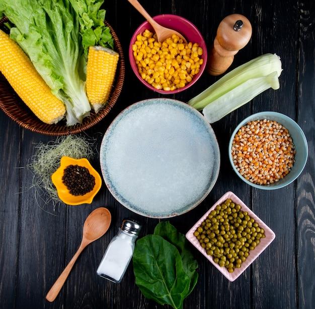 Vista superior de grãos de milho cozido sementes de alface de prato vazio com casca de milho e seda pimenta preta ervilhas verdes colher de sal espinafre no preto