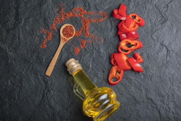 Vista superior de grãos de pimenta vermelha com fatias de pimentão fresco em fundo preto.
