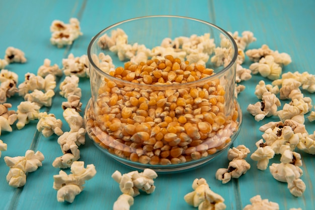 Vista superior de grãos de pipoca em uma tigela de vidro com pipocas isoladas em uma mesa de madeira azul