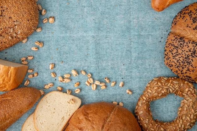 Vista superior de grãos e diferentes tipos de pão como baguete de bagel branco sobre fundo azul, com espaço de cópia