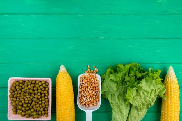 Vista superior de grãos e sementes de milho com alface de ervilhas verdes na superfície verde, com espaço de cópia