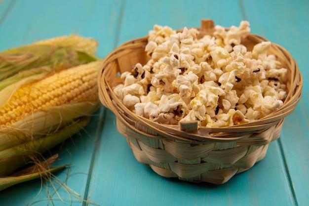 Vista superior de grãos saudáveis com cabelo com pipocas em um balde sobre uma mesa de madeira azul